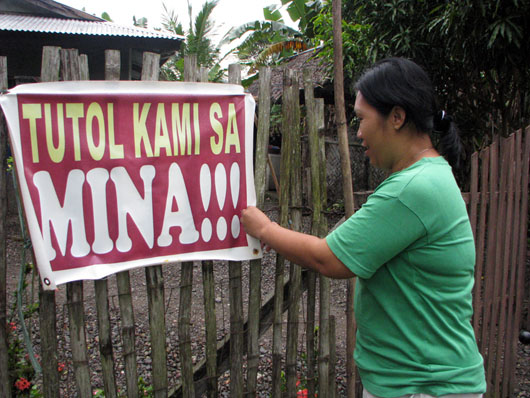 lady hanging sign in protest to mine in Philippines